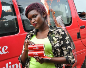 Fille poses with her personalized branded Coca-Cola cans bearing her name.