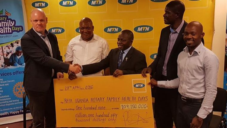 MTN CEO,Brian Gouldie (Extreme Left) hands over dummy cheque worth UGX 109,150,000 to the Rotary Uganda Team lead by Mr. Stephen Mwanje ( 2nd Left) to avail free treatment for all in the 'Rotary Health Days' project.