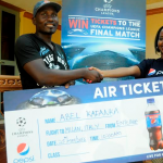 Tracy Kakuru Pepsi brand executive hands over a dummy ticket for an all-expense paid for trip to Milan Italy to Abel Kafanka. Kafanka is one of the three winners in the first UEFA champion's league Pepsi promo in which 10 Ugandans will be taken to Italy to watch the finals of the champion's league live in San Siro stadium.