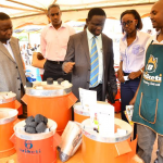 James Banaabe Commissioner Energy Efficiency and Conservation Department Ministry of Energy and Mineral Development (centre) flanked by D Wanjohu from Global Alliance for Clean Cookstoves visit one of the stalls set up during the FumbAlive Launch held at Wandegeya Market. The FumbaAlive campaign is aimed at encouraging efficient energy use to save money, time and life
