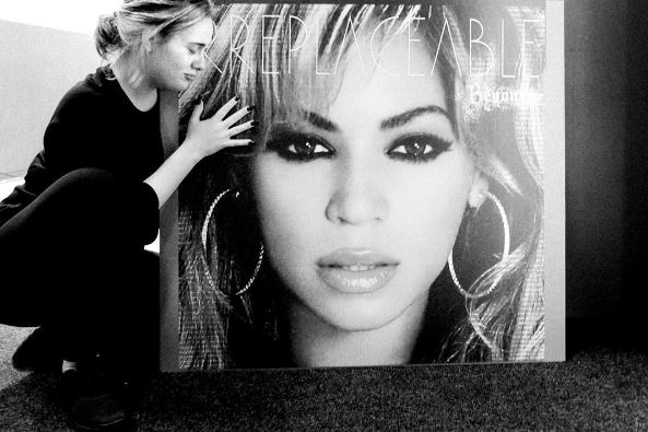 Adele hugs a picture of Beyonce