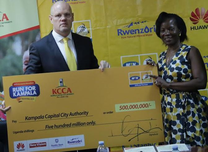 MTN's CEO Brian Gouldie handing over a dummy cheque of MTN Marathon proceeds worth shs.500 million to the Executive Director of Kampala Capital City Authority (KCCA) Jenifer Musisi.