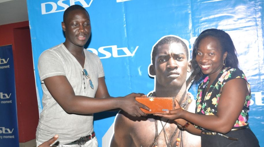 Tina Wamala (R) PR Manager Multichoice Uganda hands over a incense box to Kabs Haloha one of the guests at the Roots private screening at Century Cinemax.