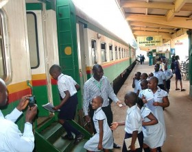 Charles Ssentongo, the RVR's senior concession and compliance officer in charge of passenger services welcomes students of Victorious Primary School on board a train to experience a commuter train journey