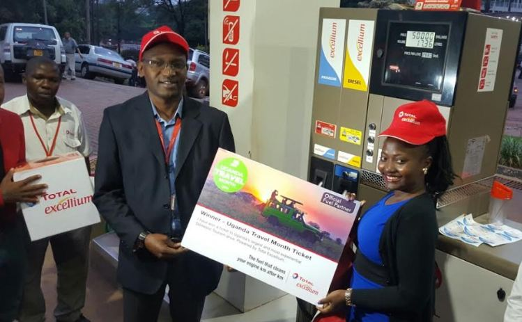 Ted Mugisa, (L) the Sales and Marketing Manager Total Uganda, hands over a ticket to the winners of the Uganda Travel Month Competition.
