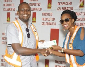 UBL's Marketing Director, Juliana Kagwa hands UBL Head of Beer, Mark Mugisha a reward for being a safety champion.