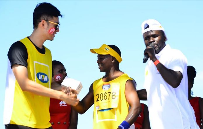 (L-R) Patrick Tong, PR Director of Huawei Uganda hands over a Huawei Y3 Lite smartphone to a lucky winner as comedian MC Madrat comments during the MTN Marathon on 20th November 2016.
