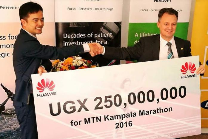 Huawei MD Mr. Stanley Chyn (L) giving a dummy cheque of Ugx 250 million to Mr. Wim Vanhelleputte, the Chief Executive Officer of MTN Uganda
