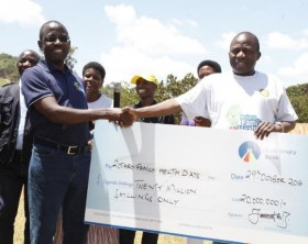 The General Manager Finance Centenary bank, Godfrey Byekwaso handing over a dummy check of 20M shillings to Chairman of the Uganda Rotary Cancer Program, Stephen Mwange