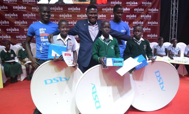 Norbert Mao (centre) poses with pupils who won the individual national Spelling Bee competition and their DSTV kits courtesy of DSTV Uganda, one of the sponsors. In the background are the DSTV sales personnel.