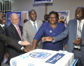 Stanbic Bank officials cut a cake at the launch of the new Stanbic Bank Branch in Hoima town standing from left to right are; Francis Omuse Stanbic branch Manager Hoima Town, Stanbic Banks Executive Director and head of Personal and Business Banking Kevin Wingfield (2nd Left), Hoima LC V Chairman Kadir Kirungi (Centre) ,the Regional Manager West, Mercy Sande (2nd right) and the Head of Customer Channels, Shem Kakembo (1st right).