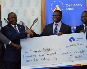 L-R: Michael Jjingo, Chief Manager Business Growth Centenary bank, Fabian Kasi, Managing Director Centenary bank handing over 210 million shilling dummy cheque to Charles Peter Mayiga the Katikkiro of Buganda and Buganda Officials.