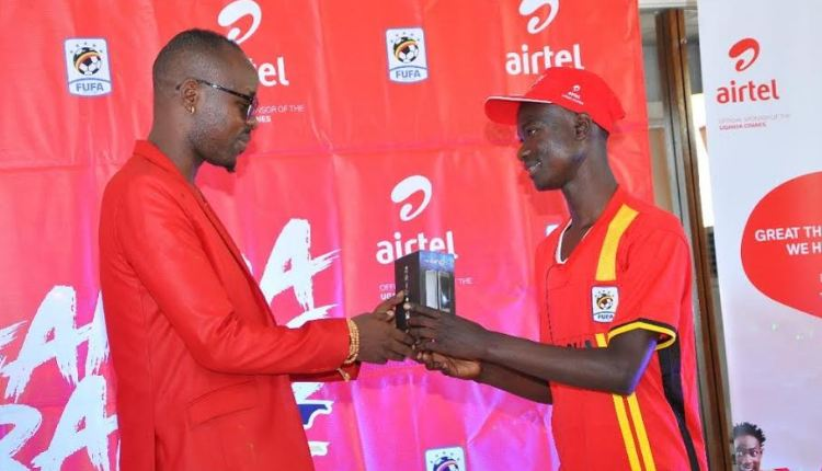 Airtel Uganda Brand Ambassador, Eddy Kenzo hands over a smartphone to one of the lucky winners during the final draw of the Tulumbe AFCON campaign at Airtel head offices.