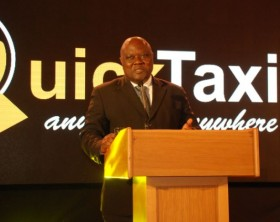 Minister of State for Transport Hon. Bagiire Aggrey addressing guests at the official launch of Quick Taxi in Uganda.
