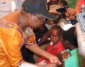 Dr. Jane Acheng, Minister of Health injects a nursing student to launch the Meningitis A Mass Immunisation campaign at the Omoro district headquarters.