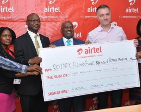 Airtel Managing Director, Anwar Soussa and Rotary blood Bank chairman, Emmanuel Katongole, Airtel staff pose a photo with a dummy cheque of Ugx 30Million they handed over to Rotary.