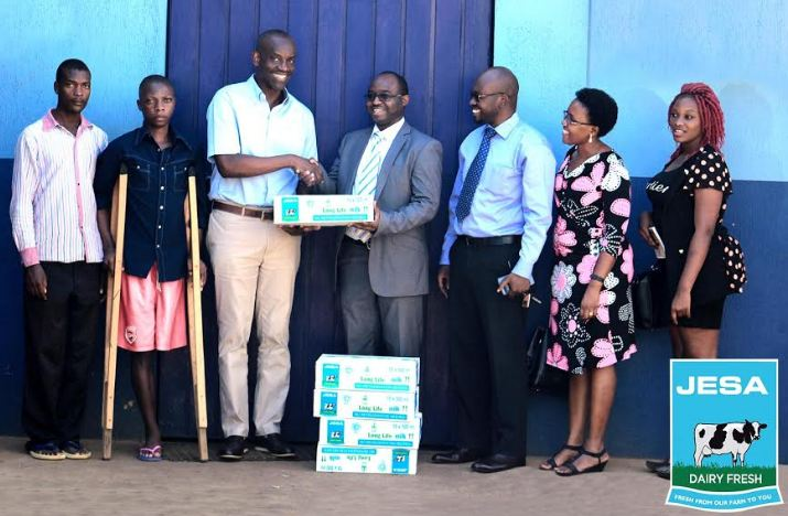 Geoffrey Mulwana, The Executive Director, Jesa Farm Dairy handing over cartons of Jesa Milk to the Uganda Cancer society