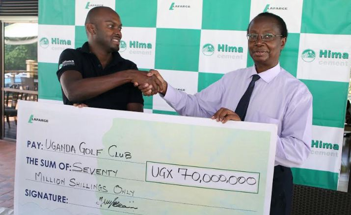Charles Mugasa (L), the Hima Cement Marketing manager hands over a dummy cheque to Prof. Anthony Kerali, the Uganda Golf Club Captain.