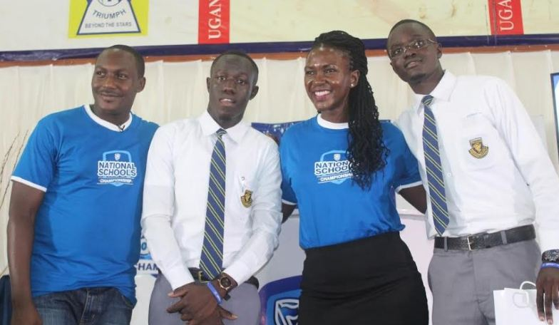 Cathy Adengo, Head of CSI and Communications Stanbic Bank (2nd right) and Brain Mulondo the quiz master of the Stanbic National Schools Championship pose for a group photo with students from Teso College Aloet who emerged as winners at the Eastern regional competition of National School Championships.