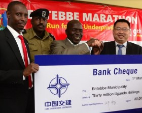 Mr Charles Magumba the Entebbe Municipality Town Clerk, Mr Godfrey Ninsiima the District Police Commander Entebbe, His Worship Vicent De Paul the Mayor Entebbe Municipality Council, and Mr Ding Jian Ming the deputy Managing Director China Communications Construction Company pose for a photo during the launch on the Entebbe Marathon at Entebbe Municipality offices.