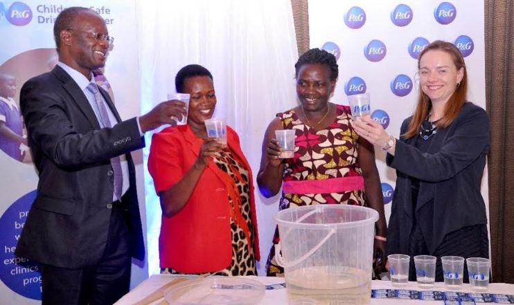 Commissioner of Water and Environmental Sector, Engineer Disan Ssozi (L), and Procter & Gamble CSDW Program Director, Ms Allison Tummon Kamphuis (R) pose for a photo with the beneficiaries during the celebration of giving away 12 billion litres of clean water.