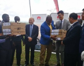 The Laptop Handover ceremony conducted by ICT Minister Hon. Frank Tumwebaze (C), Chinese Ambassador H.E. Zheng Zhuqiang (R), and Huawei Deputy MD Mr. Wangwua (L)