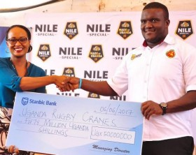 Stanbic Senior Marketing Manager Sonia Karamagi hands over a cheque worth Ugx 50 million to Uganda Rugby Cranes Captain Brian Odongo.