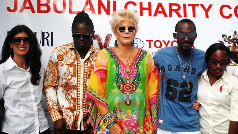 PJ Powers, Radio and Weasel pose for a photo with a team from Girl Up Initiative
