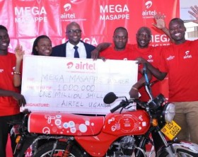 Airtel Uganda Director Legal and Regulatory Affairs Dennis Kakonge(in a suit) poses with the first group of lucky winners in the Mega Masappe promotion at Airtel Head offices.