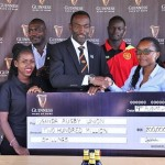 Uganda Breweries Head of Beer, Estella Muzito hands over a dummy cheque to Michael Wandera, the manager of the Uganda National 7s team.