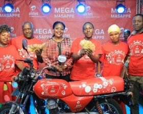 Airtel Uganda Head of Branding and Communications, Remmie Kisakye poses with the lucky winners in the Mega Massape promotion
