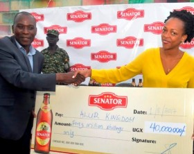 The Prime Minister of Alur Kingdom, Rt. Hon Vincent Ochaya receives a dummy cheque of UGX 40 Million from Juliana Kagwa, Uganda Breweries Marketing and Innovations Director.