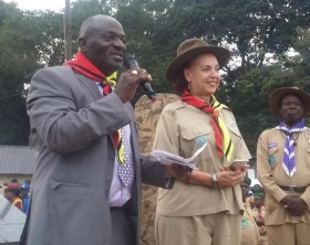 Katumba Wamala, the Minister of state for works addressing scouts at the opening ceremony of this year's national scouts' camp. Looking on is Chief Scout Dr. Maggie Kigozi.