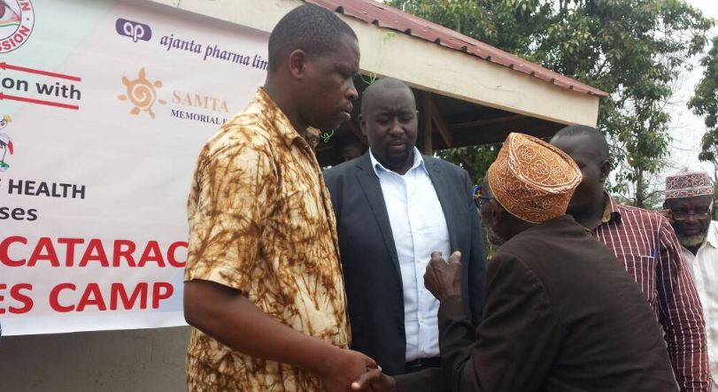 ICare Foundation Managing Director, Isaac Kigozi (C) interacts with some of the beneficiaries of the free eye camp.