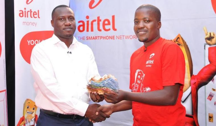 Katamba Dennis recieving the Airtel Yoola Amajja money from Airtel Uganda Sales and Distribution Director, Ali Balunywa