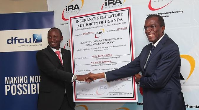 dfcu Bank's Chief of Business and Executive Director William Sekabembe receives the license from IRA CEO Ibrahim Lubega Kaddunabbi.