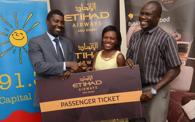 Toyin Alaran (L), the Etihad Airways General Manager for Uganda, and Apollo Onyango (R), Capital Radio Senior Sales Executive, hand over a dummy ticket to Kyomuhendo Juliet (C), the winner of the Valentines campaign. Kyomuhendo and her partner will enjoy a Valentines holiday, from 12th to 15th February, 2016, at the magnificent Yas Island Rotana Hotel in Abu Dhabi on an all-expenses paid trip.