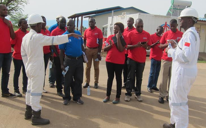 Dr Drake Kyalimpa (in blue), the head Oil and Gas Department , with students during a recent Oil fields class tour