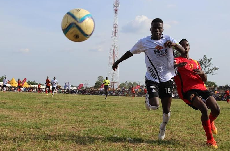 A Uganda Cranes player and a West Nile select player chase after the ball during the Uganda Cranes regional tour at Onduparaka Grounds in Arua.