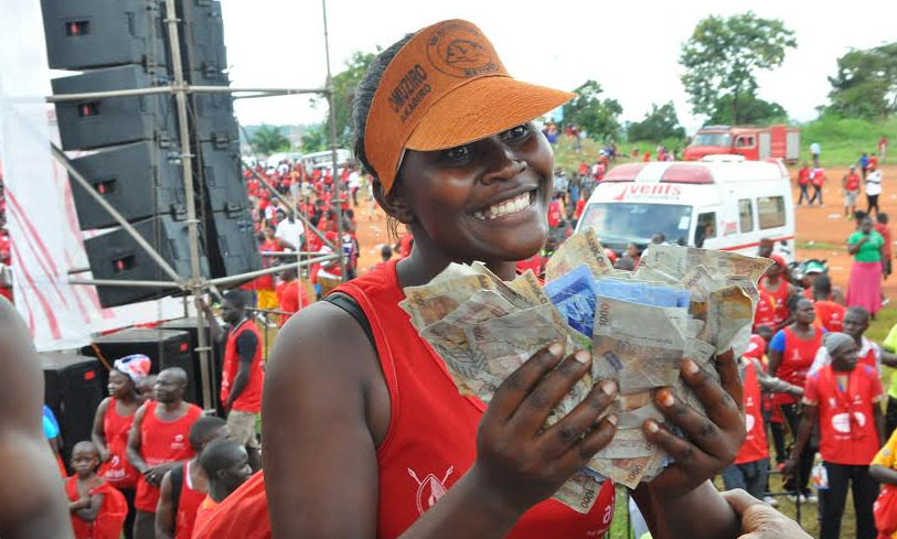 "Farida Nasegge displays the money she won during the ""Yoola Amajja"" activation at the Kabaka Birthday Run."