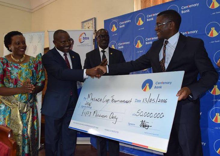 Fabian Kasi, the Managing Director, Centenary Bank (2nd R) hands over a Shs50 million Cheque to Charles Peter Mayiga the Katikiro of Buganda Kingdom (L) at Bulange, Mengo for sponsorship of the 2016 Masaza Cup. He is joined by Beatrice Lugalambi, Centenary Bank, General Manager, Business Development (R).