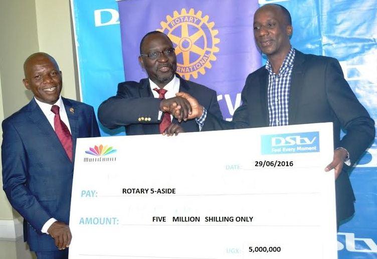 (R-L) MultiChoice Uganda General Manager , Charles Hamya hands over UGX 5 million to Governor Rotary Uganda, Robert Nsibirwa and Rotary Uganda Chairman , Francis Sentamu for the charity 5-Aside courtesy of DStv