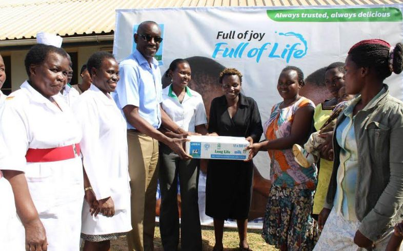 Jesa Milk Farm Dairy Managing Director, Geoffrey Mulwana hands over cartons of milk to mothers and children at Mwama Mujimu Nutrition Unit, Mulago Hospital.