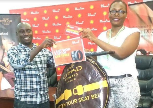 Vivo Energy Marketing Manager Jean Mugisha hands over a set of tyres to Elly Mariigaruhanga, one of the winners in the ongoing Shell V-Power club promotion.