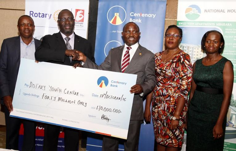 Centenary Bank MD Fabian Kasi (3R) hands over a dummy cheque to Rotary Club of Kampala North Past District Governor Robert Waggwa Nsibirwa at the bank's offices on Tuesday. Looking on is Centenary Bank Brand & Marketing Manager Immaculate Ngulumi and Chief Manager Corporate Affairs Allen Ayebare (R).