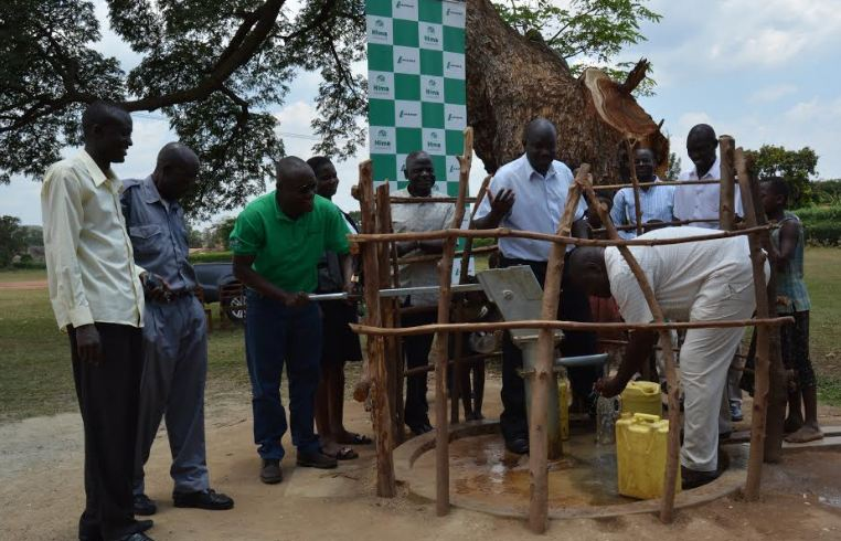 Patrick Waswa(in green t-shirt), the Logistics Director at Hima Cement pumps water from one of the boreholes donated.