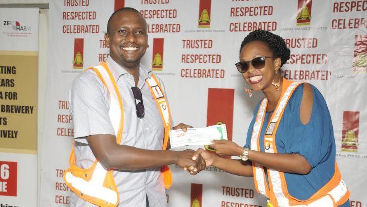UBL's Marketing Director, Juliana Kagwa hands UBL Head of Beer, Mark Mugisha a reward for being a safety champion.