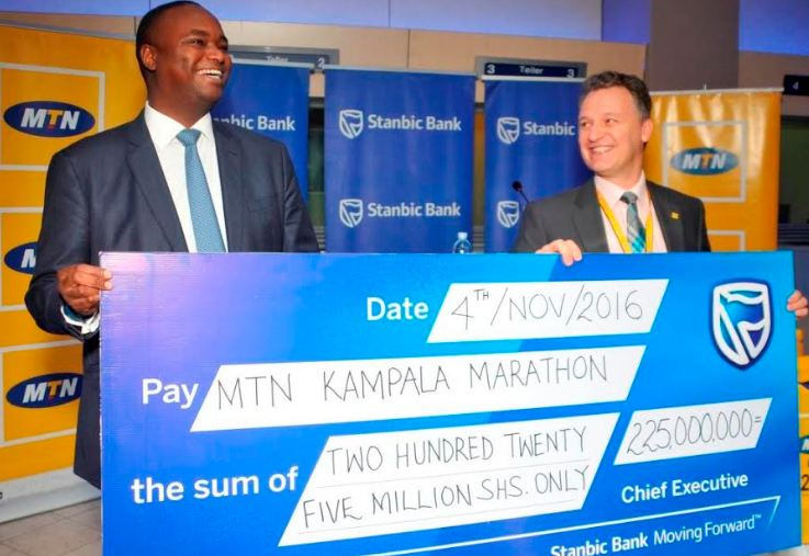 Stanbic Bank's CE Patrick Mweheire (Left) officially hands over a dummy cheque worth Shs 225 million to MTN CEO Wim Vanhelleputte as the bank's contribution towards the MTN Kampala Marathon.