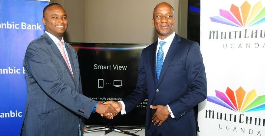 L-R : Patrick Mweheire, Stanbic Bank Chief Executive and Charles Hamya ,MultiChoice General Manager shake hands at the launch of the free online payment solutions.