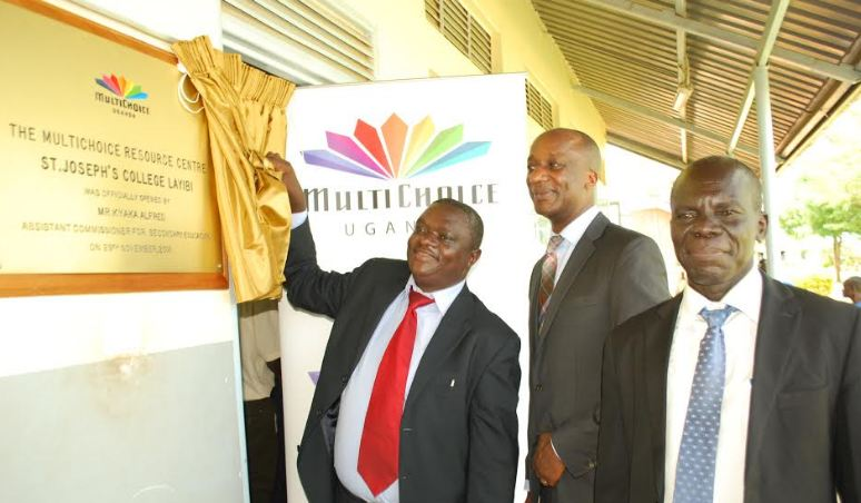 The Assistant Commissioner for Secondary Education Mr. Alfred Kyaka (left) unveils a plaque at the launch of the MultiChoice Resource Centres in Northern Uganda, Gulu district at St Joseph's College Layibi School.
